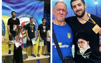 قرار گرفتن بر روی سکوی قهرمانی با پیراهن منقش به تصویر مقام معظم رهبری در اوکراین / عکس